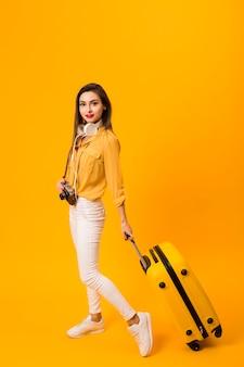Вид сбоку женщины, держащей багаж с копией пространства