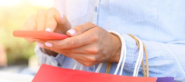 Вид сбоку женщины, держащей хозяйственные сумки и смартфон для кибер-понедельника