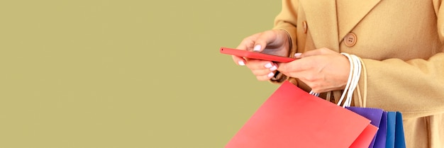 Вид сбоку женщины, держащей смартфон и хозяйственные сумки на киберпонедельник с копией пространства