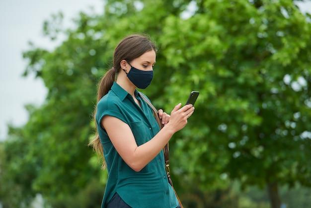 의료 얼굴 마스크에 여자의 측면보기는 전화로 뉴스를 읽고 공원에서 산책하는 동안 가방을 들고있다
