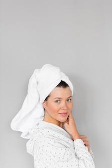 Вид сбоку женщины в халате и полотенце, показывающей красивое лицо