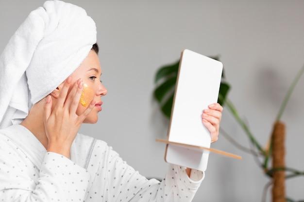 Вид сбоку женщины в халате, применяя уход за кожей с полотенцем на голове