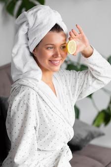 Вид сбоку женщины в халате, держащей ломтик лимона