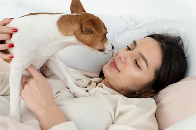彼女の犬と一緒にベッドで女性の側面図