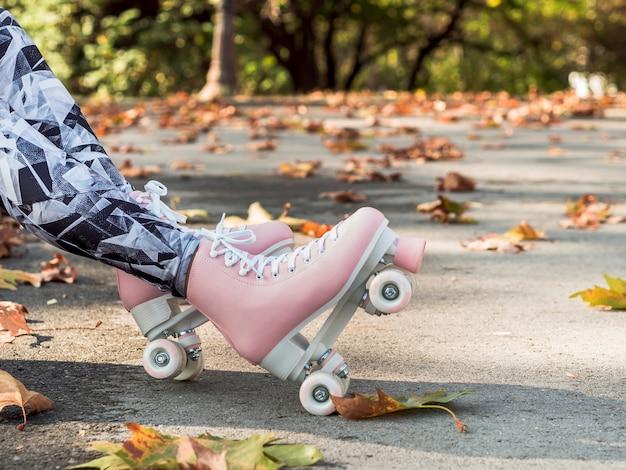 Вид сбоку женщины в леггинсах с роликовыми коньками и листьями