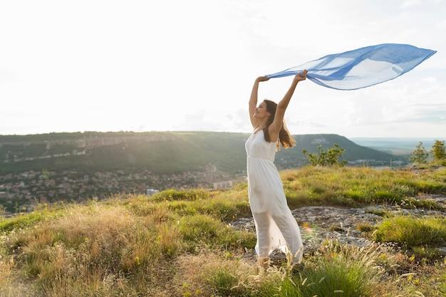 風の中のスカーフと自然の中で女性の側面図
