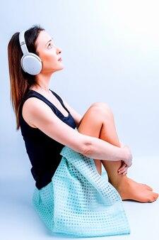 음악 헤드폰으로 바닥에 앉아 음악을 듣고 여름 옷에 여자의 측면 보기.