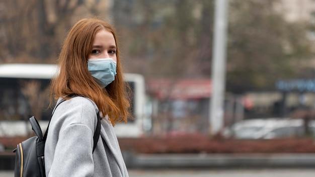 コピースペースと医療マスクを身に着けている街の女性の側面図