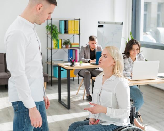 車椅子のオフィスで同僚との会話の女性の側面図