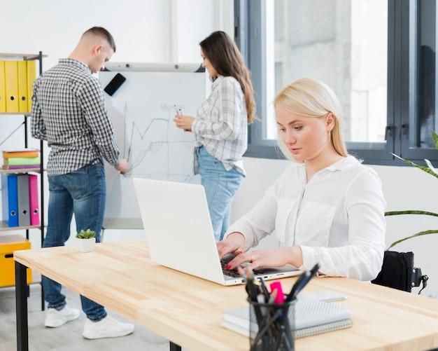 オフィスで働く車椅子の女性の側面図
