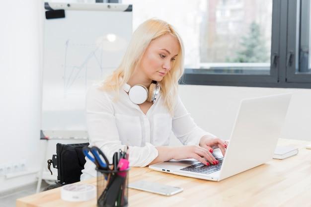 Вид сбоку женщины в инвалидной коляске, работает на ноутбуке