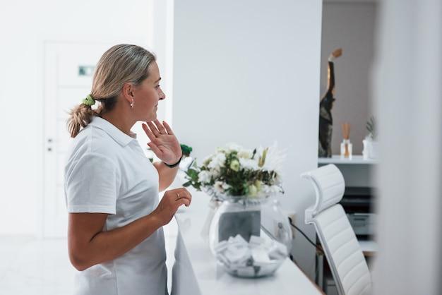 진료실에 서 있는 흰 코트를 입은 여성의 옆모습.