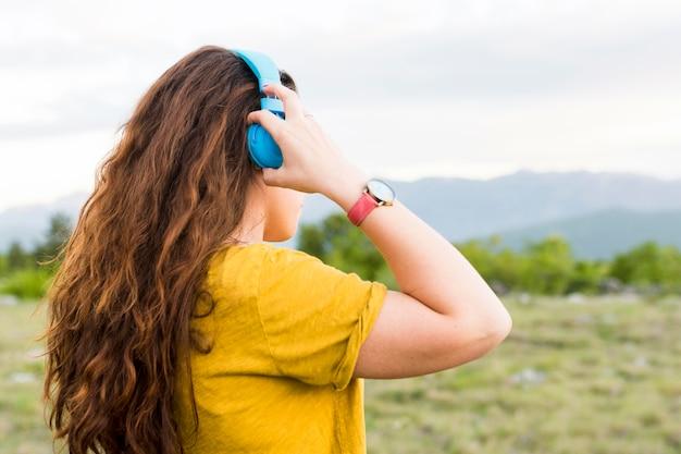 自然の中でヘッドフォンで音楽を聴く女性の側面図