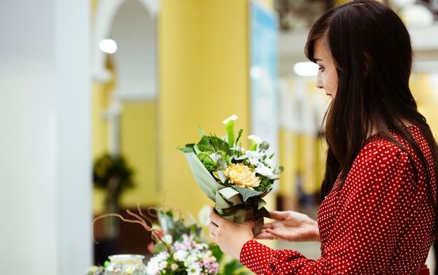 ショッピングバッグを持って植物を見ている女性の側面図
