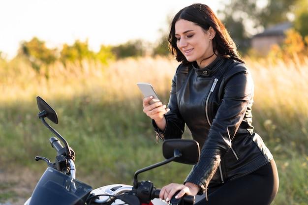 Вид сбоку на женщину, смотрящую на смартфон, прислонившись к мотоциклу