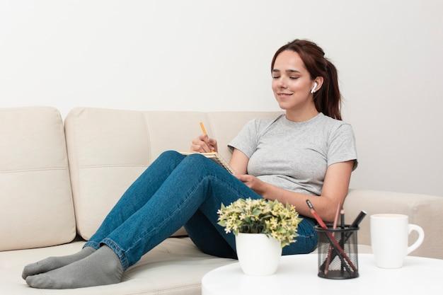 ノートに何かを書くソファの上の女性の側面図