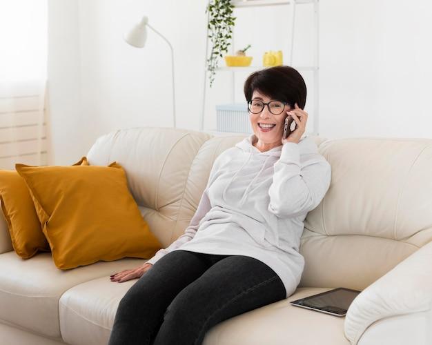スマートフォンで話しているソファの上の女性の側面図