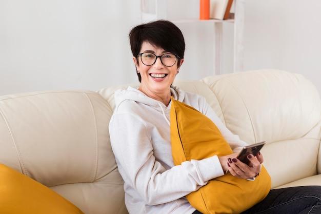スマートフォンが付いているソファーの女性の側面図