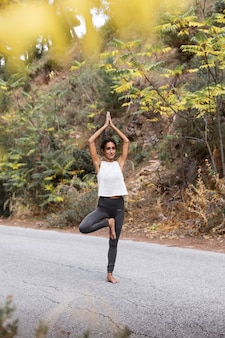 Вид сбоку женщины на дороге, занимающейся йогой