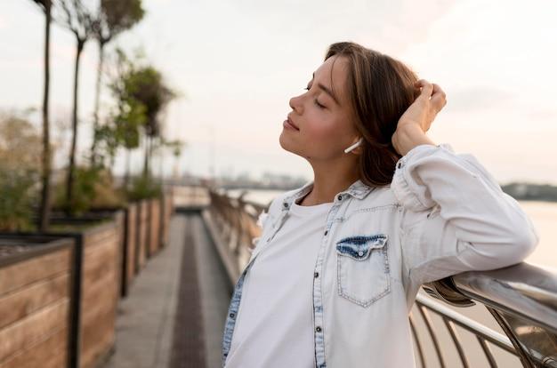 Вид сбоку женщины на открытом воздухе, наслаждающейся музыкой в наушниках