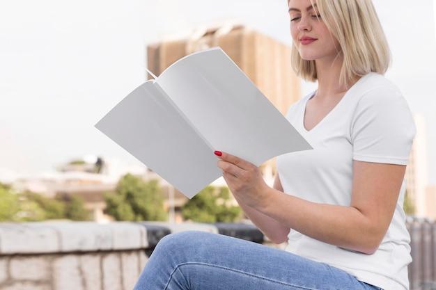 屋外で本を持って読んでいる女性の側面図