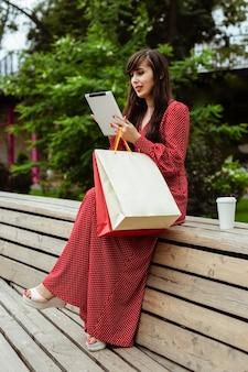 Вид сбоку женщины за пределами заказа товаров на продажу с помощью планшета