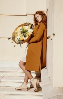 봄 꽃의 부케와 함께 밖에 서 여자의 모습