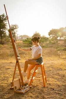 屋外のキャンバスに絵を描く女性の側面図