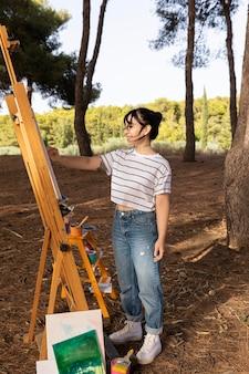 キャンバスに屋外で絵を描く女性の側面図
