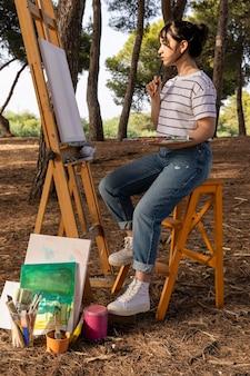 屋外で絵を描く女性の側面図