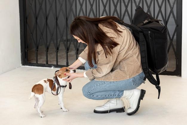 Вид сбоку женщины гладят ее милая собака