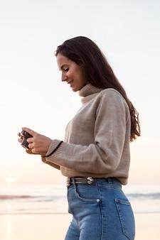 カメラで自然を撮影する女性の側面図