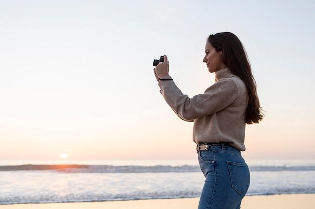 コピースペースとビーチを撮影する女性の側面図