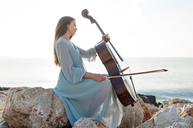 海沿いの岩の上でチェロを演奏する女性の側面図