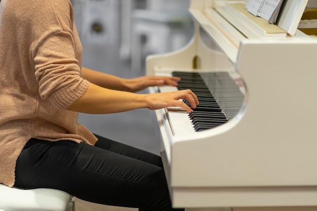 白い色のピアノを弾く女性の側面図