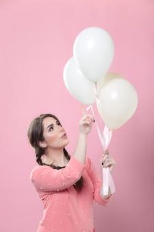 彼女が保持している風船を指している女性の側面図