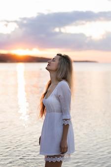 Вид сбоку женщина позирует на закате на пляже