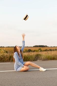 Вид сбоку женщины, позирующей посреди дороги в шляпе