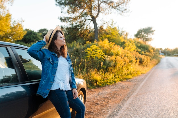 Вид сбоку женщина позирует рядом с автомобилем на открытом воздухе