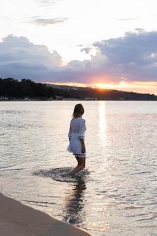 Вид сбоку женщина позирует на пляже на закате