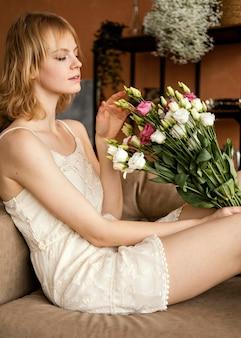 섬세한 봄 꽃의 꽃다발을 들고 소파에 포즈를 취하는 여자의 측면보기