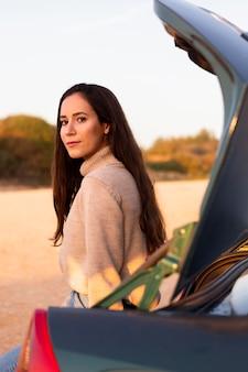 女性が彼女の車のトランクで屋外でポーズの側面図
