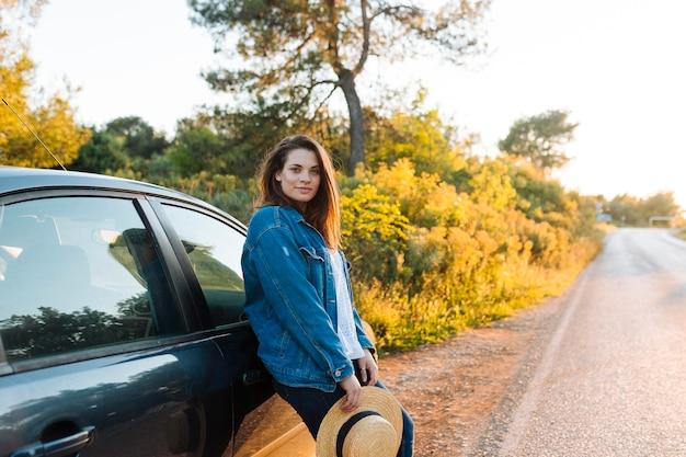 Вид сбоку женщина позирует на улице рядом с автомобилем