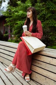 쇼핑백과 커피 한잔과 함께 밖에 포즈를 취하는 여자의 측면보기
