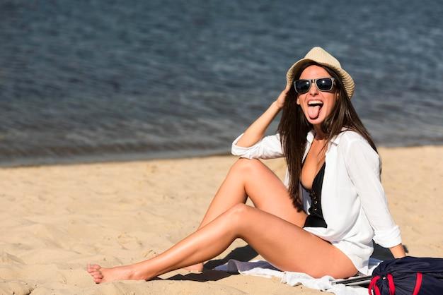 ビーチで愚かなポーズをとる女性の側面図
