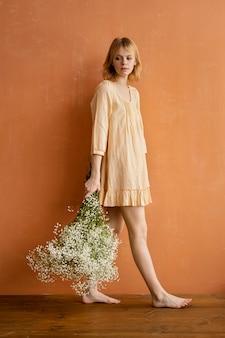 繊細な春の花の花束を持ってポーズをとる女性の側面図