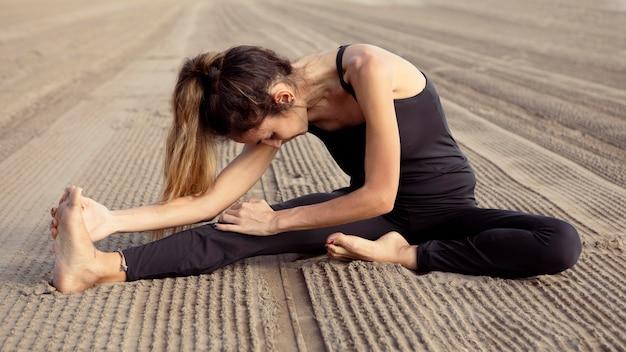 Вид сбоку женщины, практикующей йогу на песке пляжа