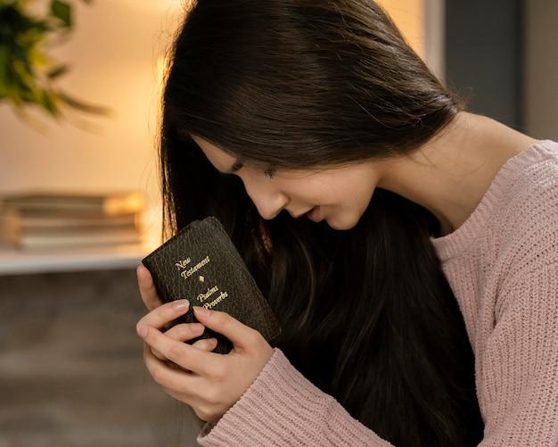 Вид сбоку женщины молятся, держа библию