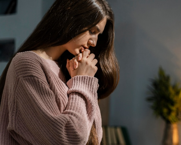 Женщина молится, вид сбоку