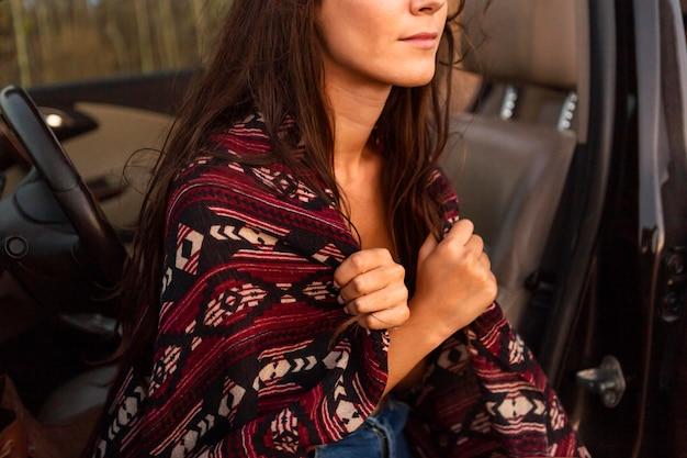 車に座っている間毛布をかぶる女の側面図
